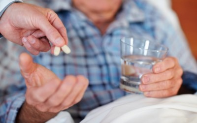 Closeup of an elderly man being given pills , focus on the medicine